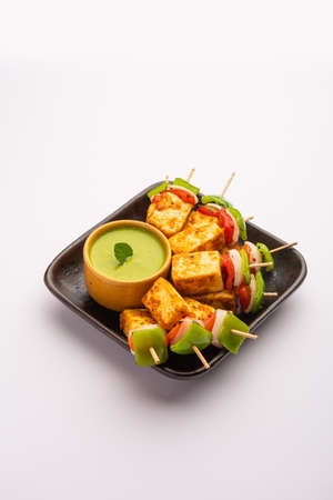 Starter snack Paneer Tikka with stick in platewith green chutney isolated over white background. Indian cuisine dish with grilled cottage cheese with vegetables and spices Standard-Bild