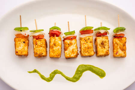 Starter snack Paneer Tikka with stick in platewith green chutney isolated over white background. Indian cuisine dish with grilled cottage cheese with vegetables and spices