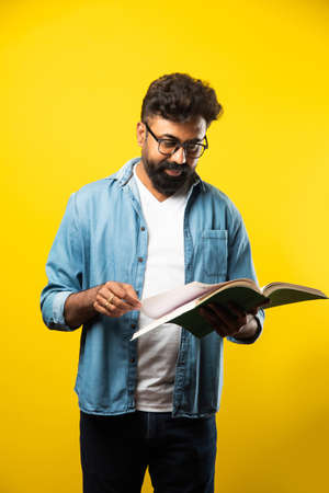 Young Indian happy man wearing eyeglasses reading book and smiling isolated over yellow background