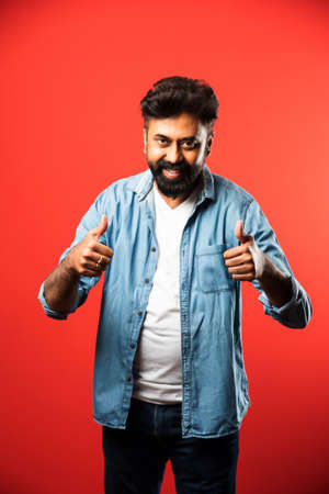 Indian asian bearded young man celebrating success against red background