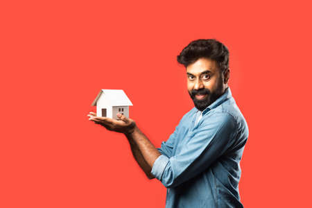 Real estate buying and people concept - Indian bearded man with miniature house model, keys and piggy bank against red background
