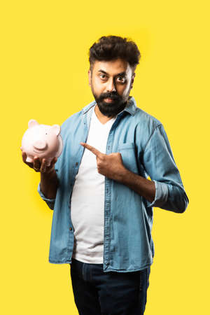 Indian asian young bearded man holding piggy bank against yellow background - people and finance concept