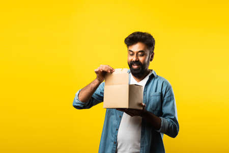 Indian asian bearded man unboxing or opening cardboard box or package against yellow background