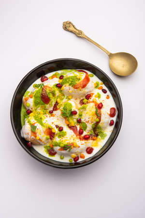 Dahi vada or bhalla is a type of chaat originating from the Indian and popular throughout South Asia. It is prepared by soaking vadas in thick dahi or curd. selective focus