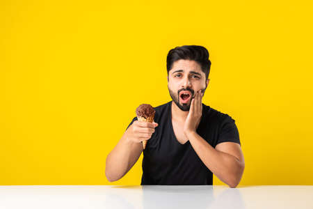 Indian young man eating ice cream in cone and having teeth ache because of cavity, sitting at table against yellow or white background Banque d'images