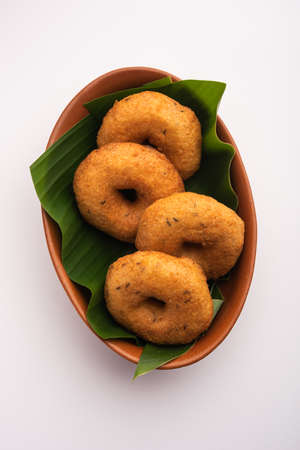South Indian Vada, Medu vada or dal vadai in plate or bowl, isolated on plain background, selective focus Banque d'images
