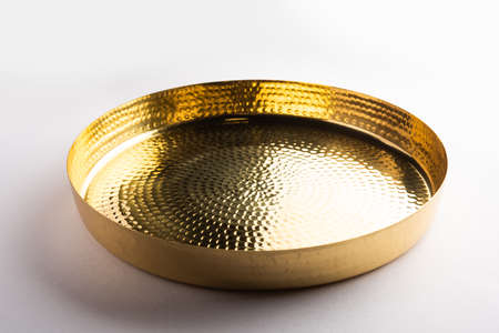 Empty oval or round shape thali or plate made up of brass, pital or gold over white background