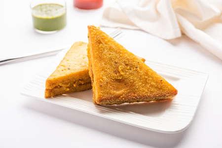 Sandwich Bread Pakora or triangle shape pakoda served with tomato ketchup, green chutney, Popular indian tea-time snack Reklamní fotografie