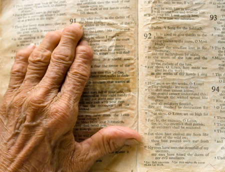 Arthritic Hand on Yellowed Page of Bible