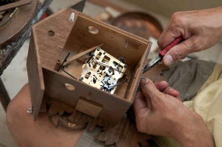 reloj cucu: Artesano en el proceso de reparación de un reloj cucú Foto de archivo