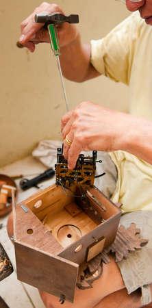 cuckoo clock: Artesano ancianos reparaci�n de un reloj de cuco