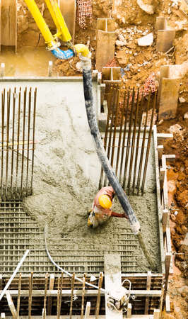 Construction worker directing cement hose to corner of foundation block Stock Photo