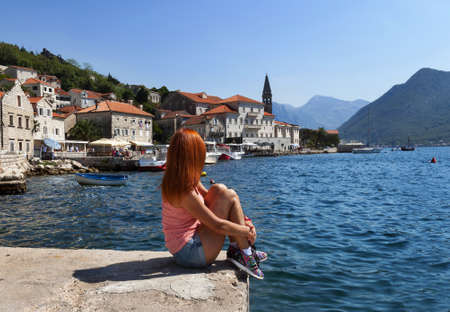 red head woman: Red head woman is seatting on the pier and looking to sea and mountains. Coastline with houses on the one hand and sea on the other