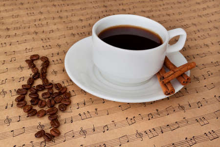 sheetmusic: Cup of black coffee on the sheet music with cinnamon and clef from coffee beans Stock Photo
