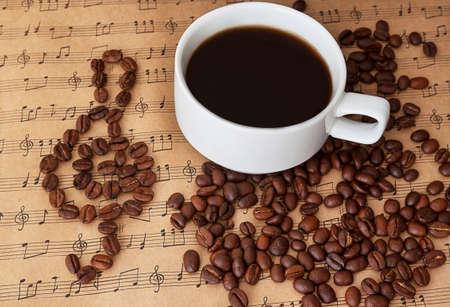 sheetmusic: Cup of black coffee on the sheet music with cinnamon and beans of coffe and clef from this beans