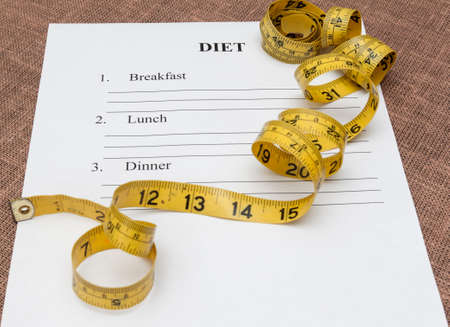 weightloss plan: paper with blank diet plan and yellow measure tape on table Stock Photo