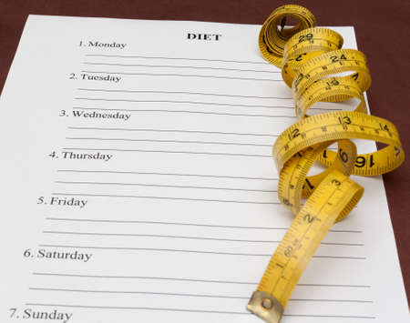 diet plan: paper with weekly blank diet plan and yellow measure tape