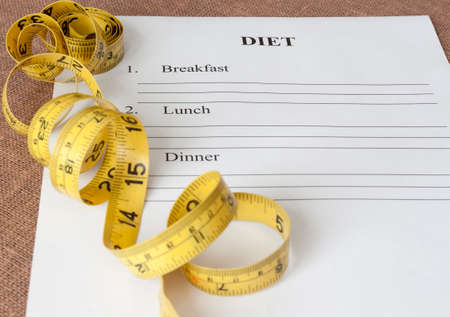 diet plan: paper with blank diet plan and yellow measure tape Stock Photo