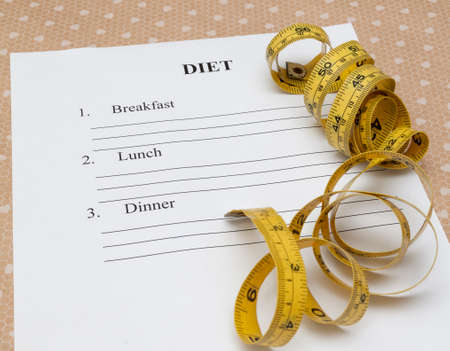 weightloss plan: paper with diet plan and roll yellow measure tape on yable Stock Photo