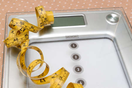 dieting: Dieting weightloss slim down concept. Closeup measuring tape on white weight scale Stock Photo