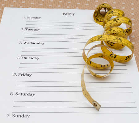 weightloss plan: paper with week diet plan and yellow measure tape on table