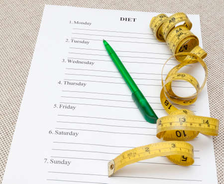 weightloss plan: sheet of paper with week diet plan, pen and yellow measure tape Stock Photo