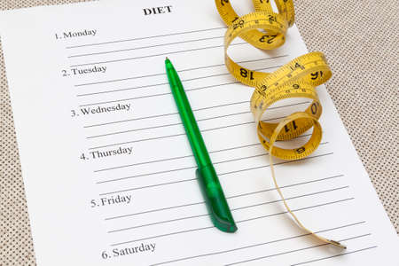 weightloss plan: paper with blank diet plan, pen and yellow measure tape on table