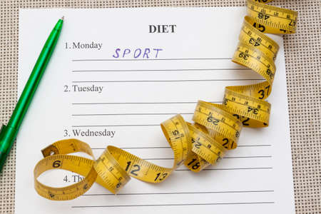 diet plan: paper with day blank diet plan and yellow measure tape