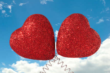 Two Glittery Red Hearts on Cloudy Blue Sky Background photo