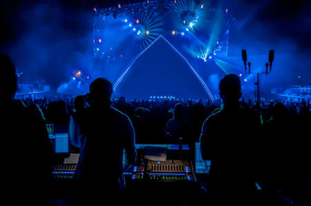 大勢のサウンド エンジニアと空のステージを見据えて、フォア グラウンドで机を混合