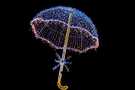 seasonal light display: Umbrella lit by fairy lights on isolated on black background