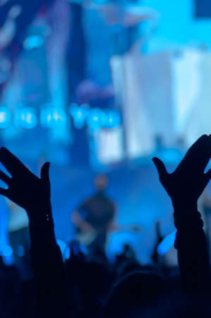 hands raised: Open hands raised up in foreground with anonymous guitar player on stage in background Stock Photo
