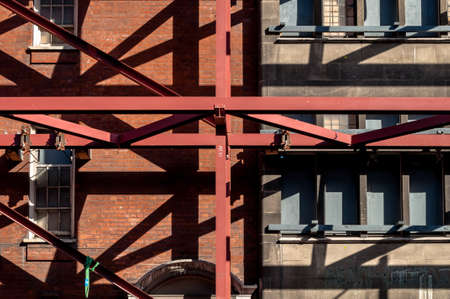 girders: Criss-Cross of beans and steel girders on the exterior of old building