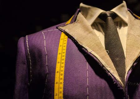 黄色のテープ メジャーでマネキンに進行中の作業スーツ