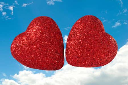 red glittery: Due brillantini Cuori Rossi galleggiano in un cielo nuvoloso blu