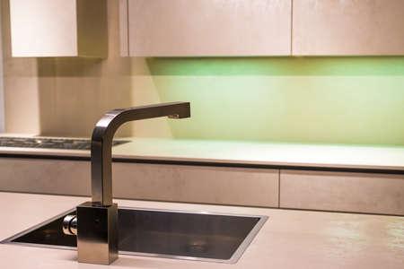 シンプルなキッチンに現代的なステンレスのタップ