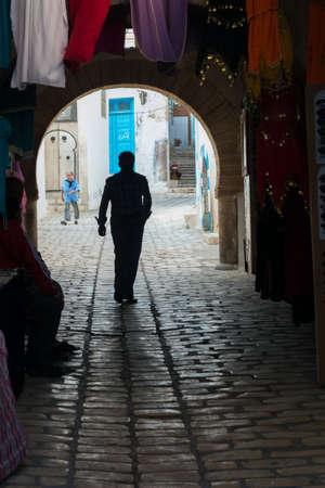 Silhouette of Man Walking in Old Tunisian Medina photo
