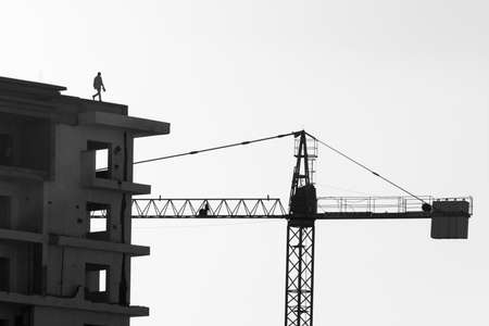 dangerous ideas: Man Walking on Roof of Contruction Site Building with Crane Stock Photo