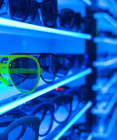 Stylish Sunglasses on Blue Neon Shelf in Shop photo