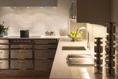 Underlighting と銀の蝋燭の棒でスタイリッシュな近代現代のキッチン