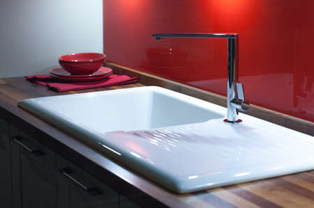 on tap: Modern Stylish Kitchen with Wooden Counter, White Enamel Sink and Modern Silver Faucet Tap Stock Photo