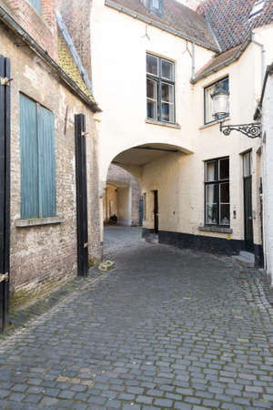 cobbled: Old Cobbled Street With Arch in Bruges, Belgium
