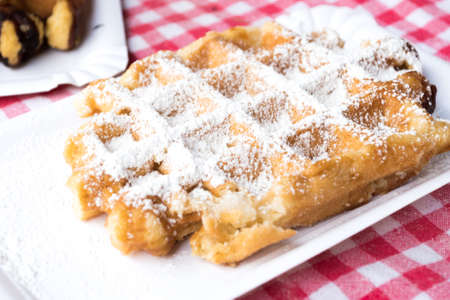 sugared: Traditional Belgian Plain Waffle Dusted with Icing Sugar on Red Checked Tablecloth