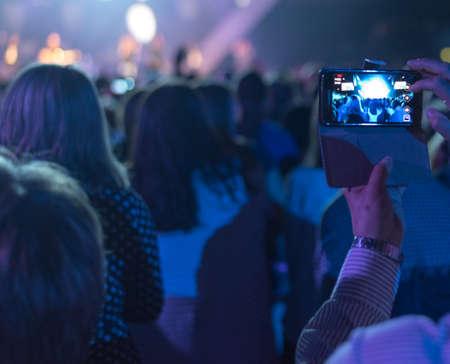 1 つの携帯電話のデバイスを持っている手と音楽コンサート 写真素材