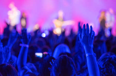 worship praise: Open hands raised up in foreground with anonymous guitar player on stage in background Stock Photo