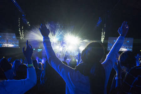 pop idol: Anonymous Woman with Arms Up in Crowd of People Looking Towards Brightly LIt Stage