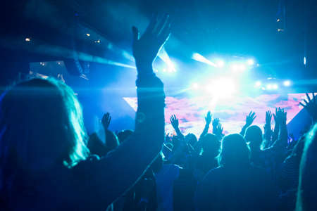 worship hands: Anonymous Woman with Arms Up in Crowd of People Looking Towards Brightly LIt Stage