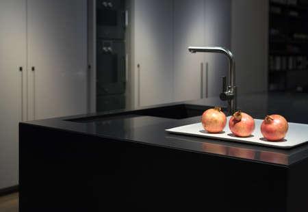 Koele en elegante, moderne en stijlvolle keuken met zwart granieten aanrechtblad