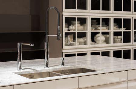 grifos: Limpie la cocina moderna con encimera de mármol blanco y Vajilla de Gabinetes en backfground.