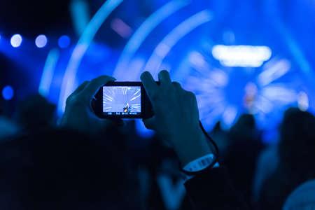 1 つの携帯電話のデバイスを両手で音楽コンサート